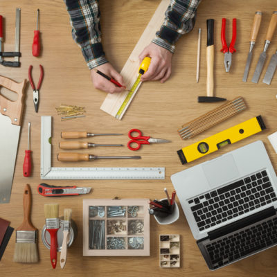 Male hands measuring a wooden plank with a tape measure with DIY work tools all around on a work table, top view